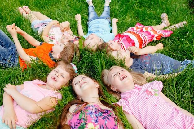 Eine gruppe glücklicher kinder, jungen und mädchen, die sich an einem sonnigen sommertag im park auf dem rasen niederlegen.