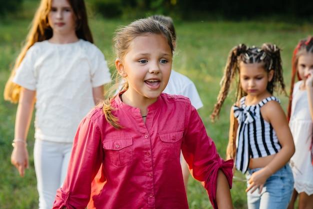 Eine gruppe glücklicher kinder rennt und spielt während des sonnenuntergangs im park. sommerkinderlager.