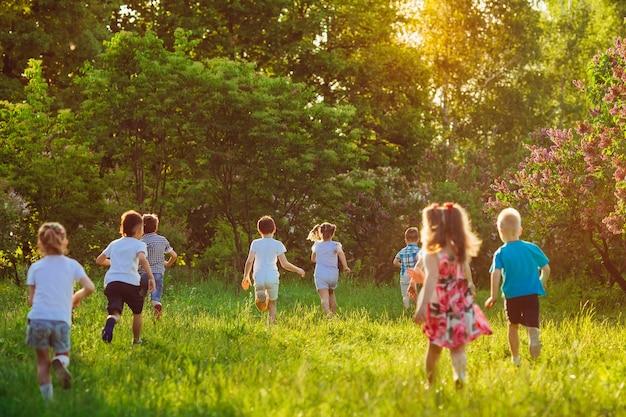 Eine gruppe glücklicher kinder von jungen und mädchen läuft an einem sonnigen sommertag im park auf dem rasen.