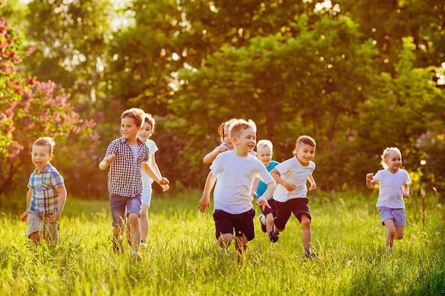 Eine gruppe glücklicher kinder von jungen und mädchen läuft an einem sonnigen sommertag im park auf dem rasen. Premium Fotos