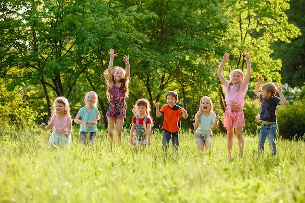 Eine gruppe glücklicher kinderjungen und mädchen, die an einem sonnigen sommertag im park auf dem gras laufen.