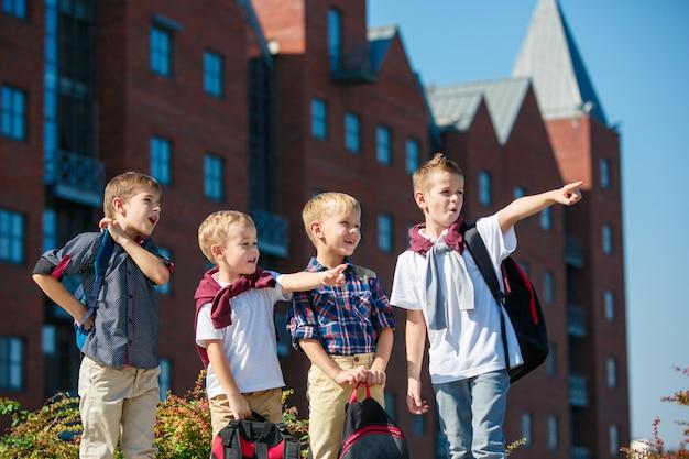 Eine gruppe glücklicher lächelnder kinder, die gegen die stadt stehen. die kindheit, kindermode, schule, bildung, freunde, lifestyle-konzept