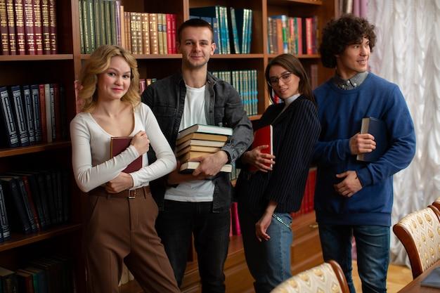 Eine gruppe glücklicher studenten, zwei männer und zwei frauen in der bibliothek nach der prüfung