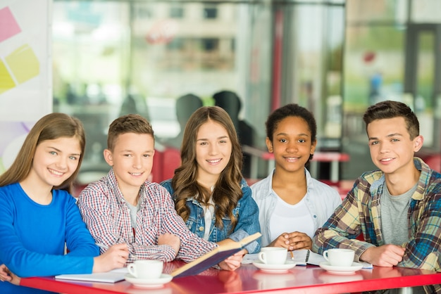 Eine gruppe jugendliche, die am tisch im café sitzen.