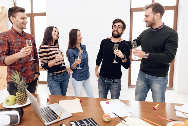 Eine gruppe junge feiernde büroangestellte.