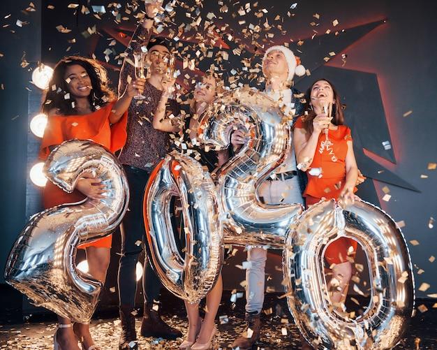 Eine gruppe junge schöne multinationale leute des spaßes, die konfettis an einer party werfen. feier des jahres 2020.
