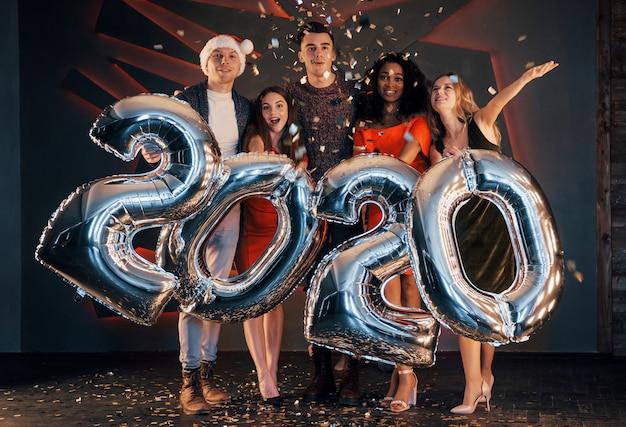 Eine gruppe junge schöne multinationale leute des spaßes, die konfettis an einer party werfen. frohes neues jahr.