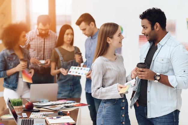 Eine gruppe junger designer arbeitet in einem hellen büro zusammen.