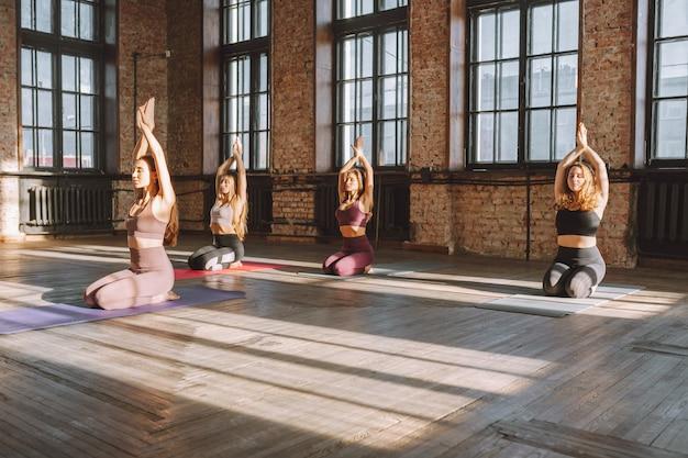 Eine gruppe junger frauen, die sporst-kleidung tragen, macht einen komplex aus stretching-yoga-asanas in einer großen loft-stilklasse an einem sonnigen tag.