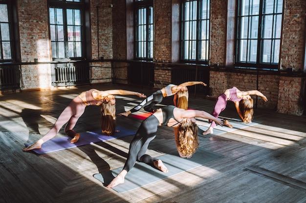 Eine gruppe junger frauen, die sporst-kleidung tragen, macht einen komplex aus stretching-yoga-asanas in einer großen loft-stilklasse an einem sonnigen tag