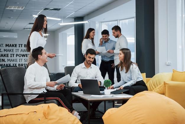 Eine gruppe junger freiberufler im büro unterhält sich und lächelt