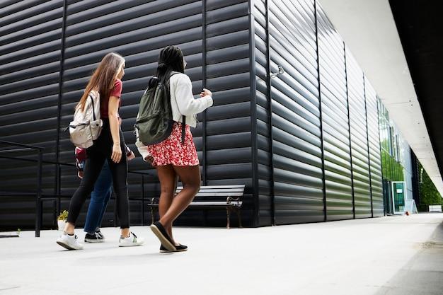 Eine gruppe junger freunde läuft auf dem campus herum