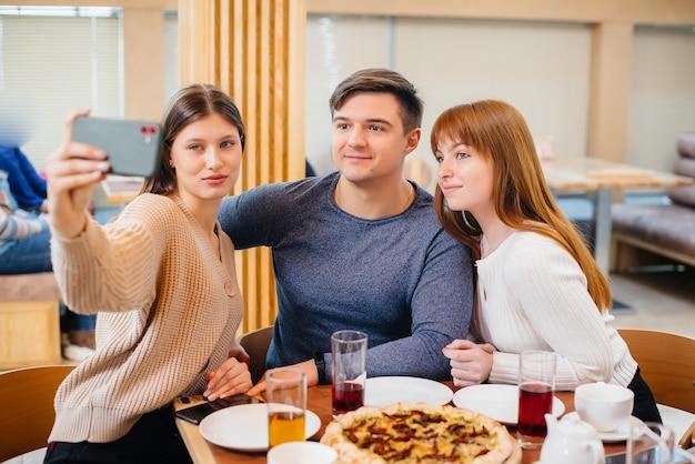 Eine gruppe junger fröhlicher freunde sitzt in einem café und redet und macht selfies am telefon. mittagessen in der pizzeria.