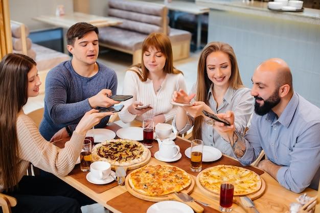 Eine gruppe junger fröhlicher freunde sitzt in einem café und redet und macht selfies am telefon