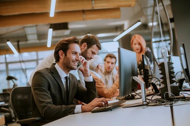 Eine gruppe junger geschäftsleute arbeitet mit desktop-computern zusammen