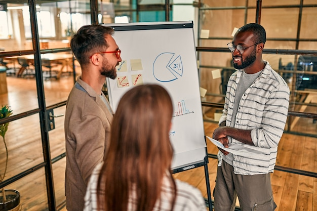 Eine gruppe junger geschäftsleute diskutiert einen geschäftsplan an einer tafel in einem modernen büro.