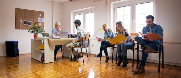 Eine gruppe junger ingenieure prüft sorgfältig die neuen aufgaben, die ihnen zugewiesen wurden, während eine von ihnen mit der schönen chefin an ihrem schreibtisch spricht