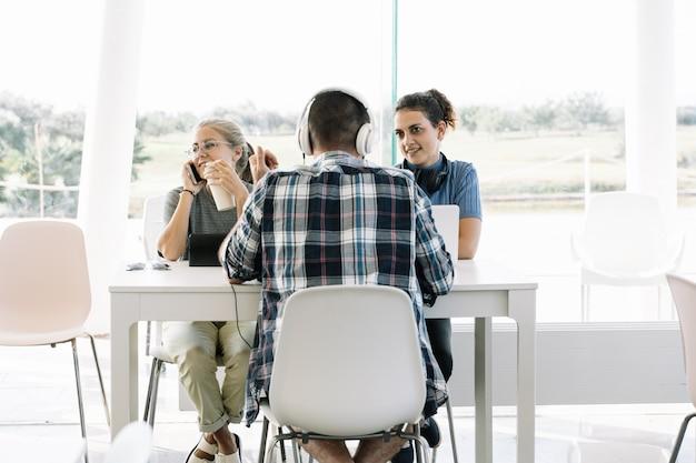Eine gruppe junger leute, die auf einem mobiltelefon und mit helmen am selben tisch mit laptops sprechen, die in einem coworking arbeiten