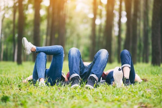 Eine gruppe junger leute, die sich auf einem grünen gras im wald hinlegen