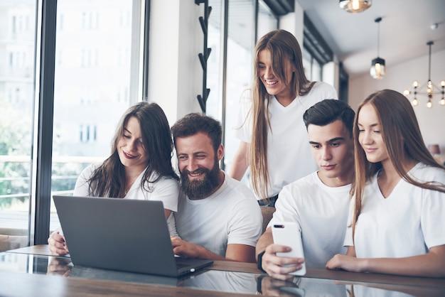 Eine gruppe junger leute mit geräten und einem laptop organisiert ein brainstorming und kommuniziert miteinander. das konzept der entwicklung eines jungen unternehmens.