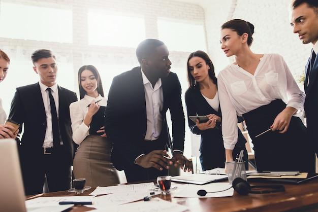 Eine gruppe junger leute veranstaltet ein brainstorming im büro.