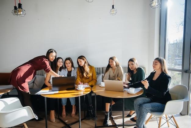 Eine gruppe junger mädchen sitzt in einem büro am computer und bespricht projekte. kommunikation und training online.