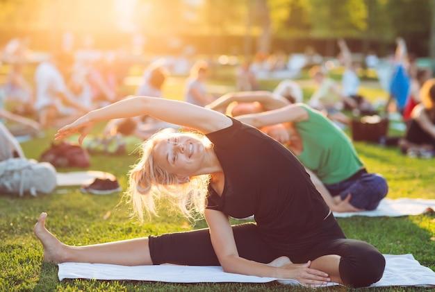 Eine gruppe junger menschen macht yoga im park bei sonnenuntergang.