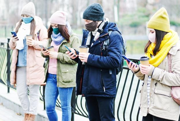 Eine gruppe junger menschen steht in einiger entfernung voneinander und hält während der coronavirus-epidemie abstand