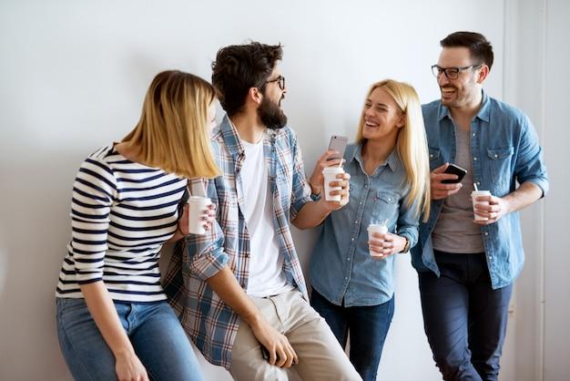 Eine gruppe junger models macht eine kaffeepause und lacht.