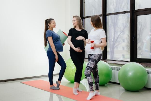 Eine gruppe junger schwangerer mädchen macht yoga und knüpft drinnen kontakte. gesunder lebensstil