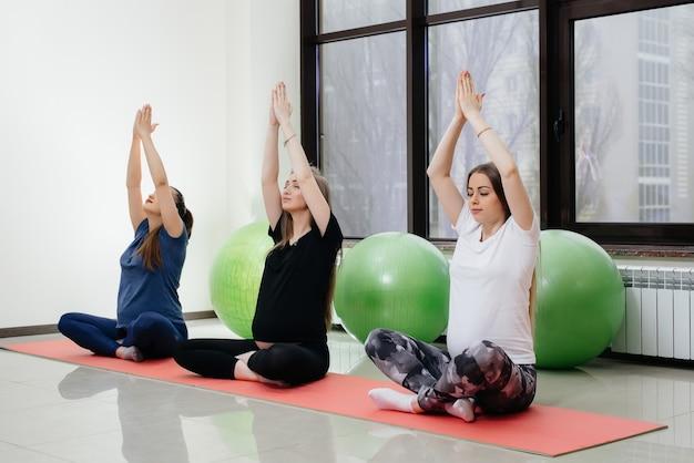 Eine gruppe junger schwangerer mädchen macht yoga und sport auf innenmatten. gesunder lebensstil