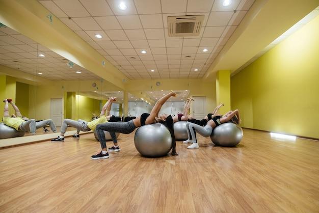 Eine gruppe junger sportlerinnen macht unter anleitung eines trainers übungen im fitnessstudio