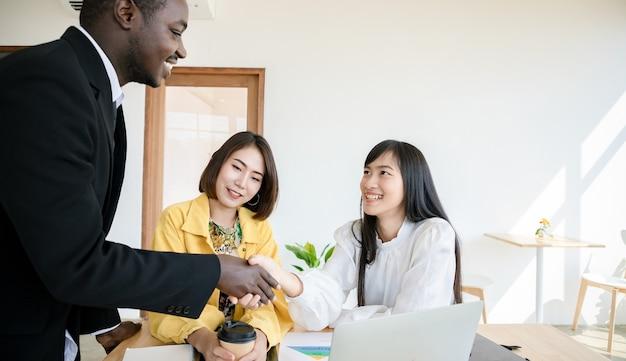 Eine gruppe junger unternehmen kooperiert und schafft vereinbarungen in der organisation. geschäftsmannführer im büro. erfolgreiche projekte und glückwünsche.