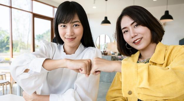 Eine gruppe junger unternehmen kooperiert und schafft vereinbarungen in der organisation im café. erfolgreiche projekte und glückwünsche. fauststoß oder knöchelstoßkonzept.