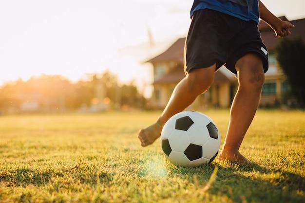 Eine gruppe kinder, die fußballfußball für übung im ländlichen gebiet der gemeinschaft unter dem sonnenuntergang spielen