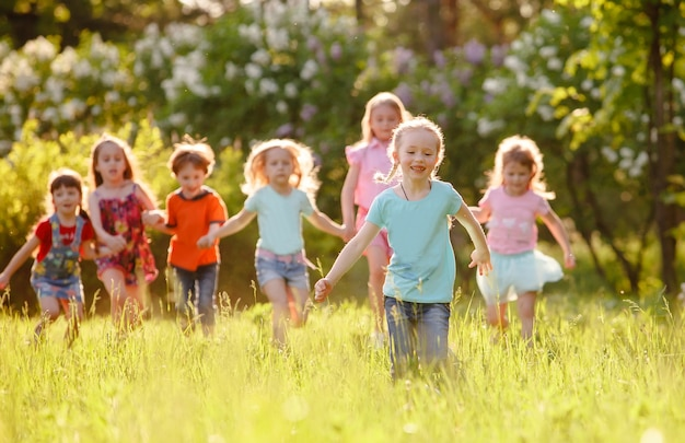 Eine gruppe kinder, die in den park auf einem grünen gozon spielen und laufen.