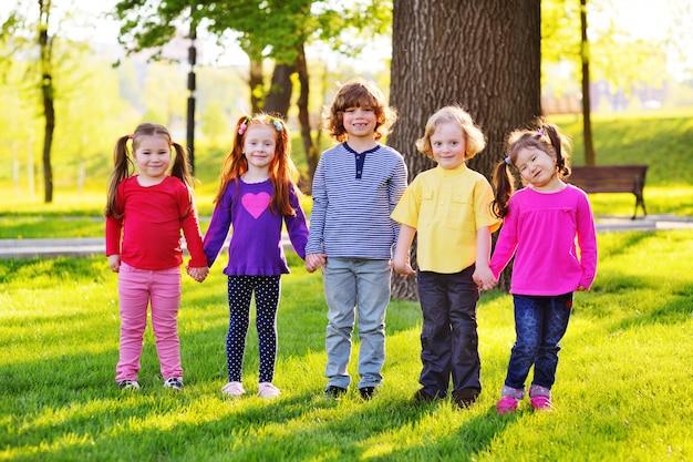 Eine gruppe kleine kinder, die händchenhalten auf einem hintergrund des grases, des baums und des parks lächeln.