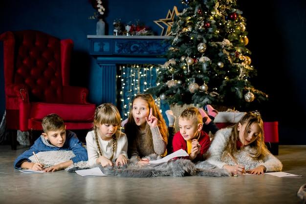 Eine gruppe kleiner kinder auf dem hintergrund eines weihnachtsbaumes und schreiben einen brief an den weihnachtsmann.
