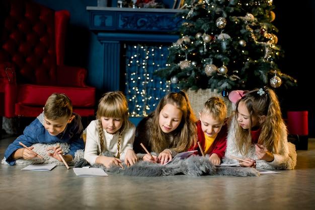 Eine gruppe kleiner kinder liegt auf einer warmen wolldecke auf dem hintergrund eines weihnachtsbaumes