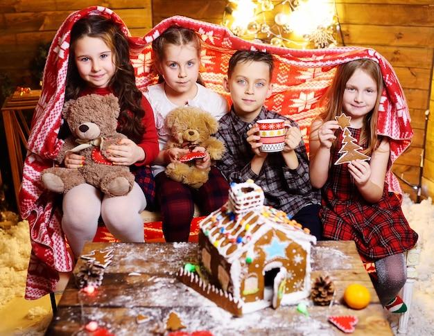 Eine gruppe kleiner kinder spielt mit spielzeug, weihnachtsdekor und lebkuchenhaus.