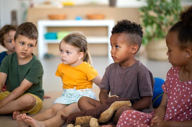 Eine gruppe kleiner kindergartenkinder, die drinnen im klassenzimmer auf dem boden sitzen und dem lehrer zuhören