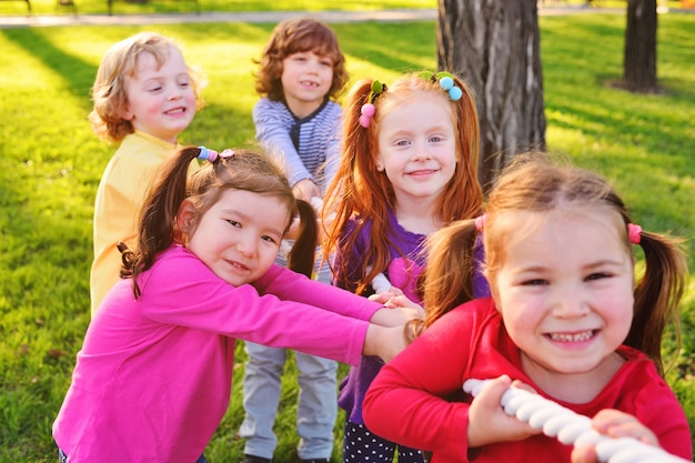 Eine gruppe kleiner vorschulkinder spielt im park ein tauziehen.