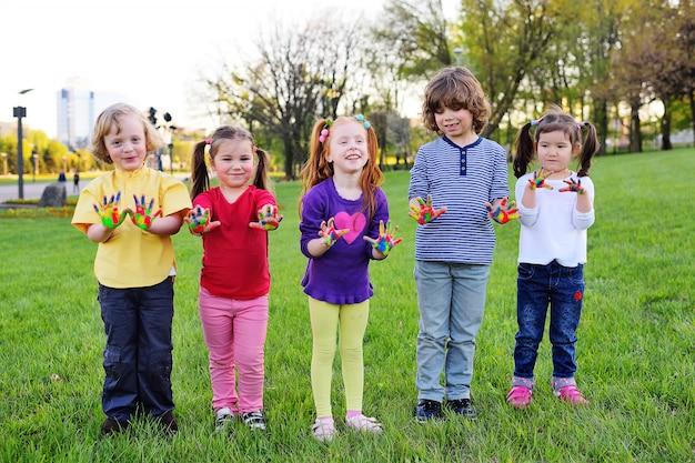 Eine gruppe kleinkinder mit den händen, die in der farbfarbe schmutzig sind, spielen im park.