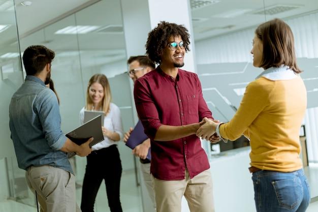 Eine gruppe kreativer junger leute, die im büro stehen