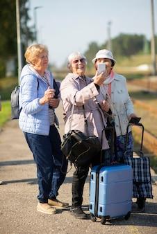 Eine gruppe lächelnder älterer frauen nimmt ein selbstporträt auf einem bahnsteig auf, der darauf wartet, dass ein zug fährt