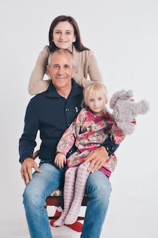 Eine gruppe lächelnder menschen bildete eine säule. glücklicher mann unter frauen, erwachsenen, kindern, spielzeug. geschenk für kinder, familientag