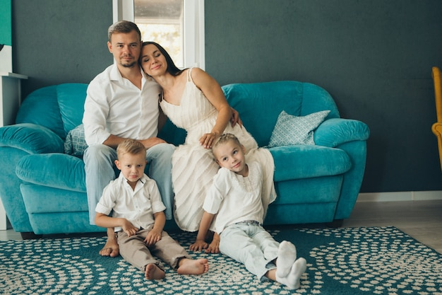 Eine gruppe lächelnder menschen: mann, frau, kinder. glückliche familie mit liebe auf blauem sofa
