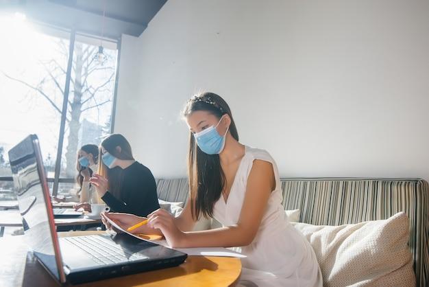 Eine gruppe maskierter mädchen hält in einem café soziale distanz, wenn sie an laptops arbeitet.
