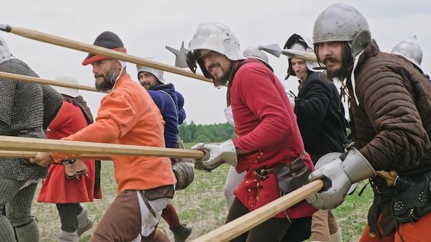 Eine gruppe mittelalterlicher ritter mit speeren, die angreifen. ritter sind in mittelalterliche kleidung gekleidet.