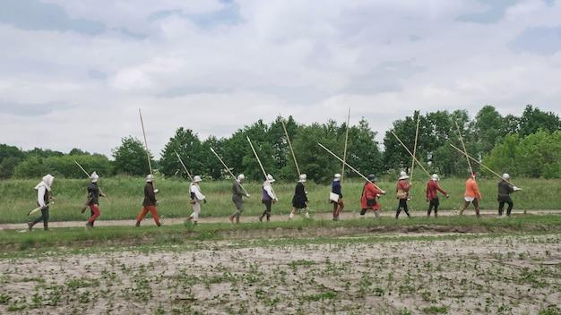 Eine gruppe mittelalterlicher ritter zieht in die schlacht. krieger mit speeren, schwertern, schleifen und helmen auf den köpfen.